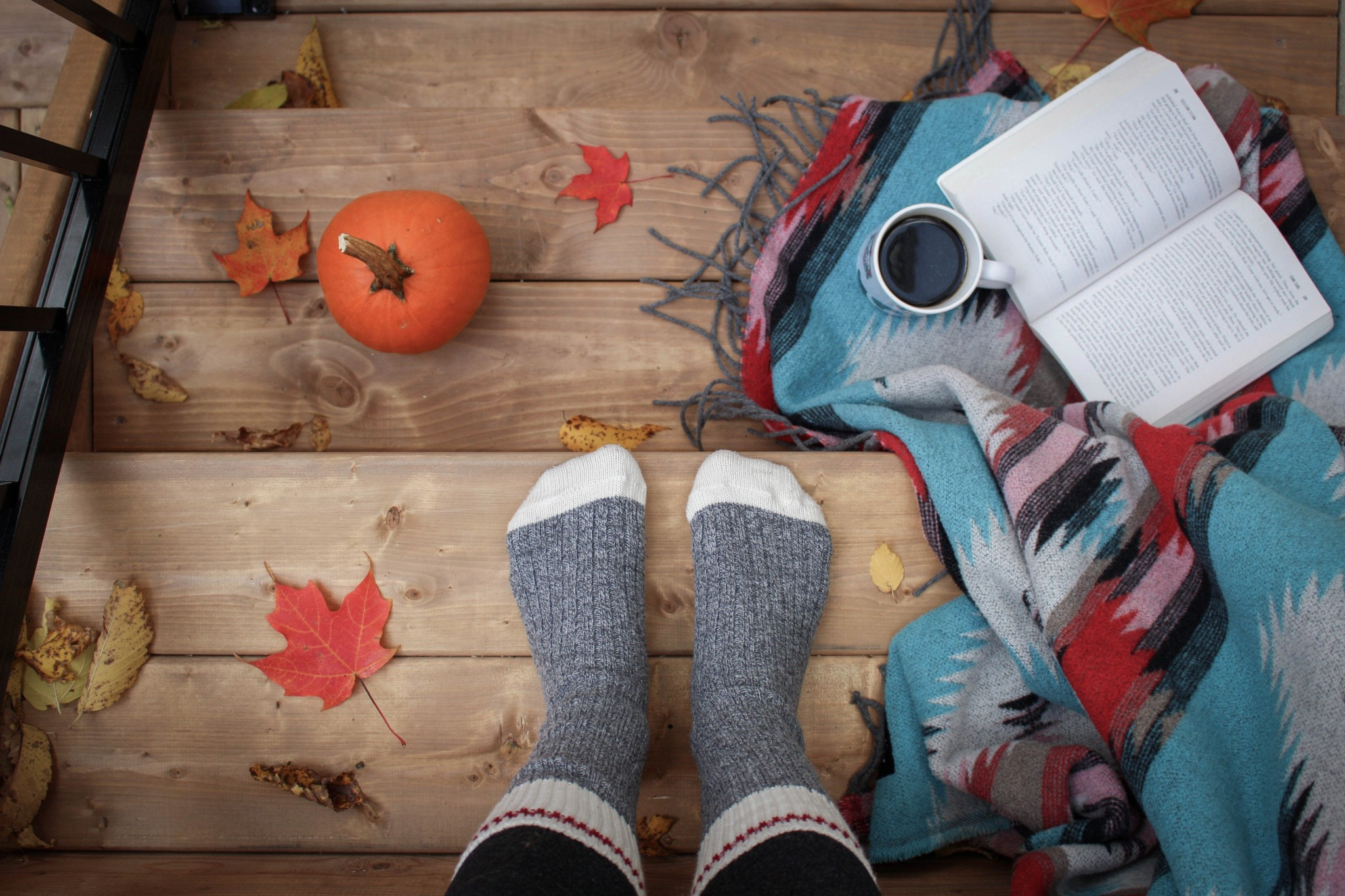Practicing self-care in the fall with warm socks, a book, coffee, blanket, pumpkins and leaves.